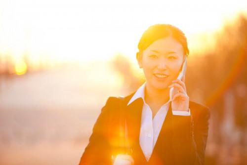 夕日の中スマホで通話する女性